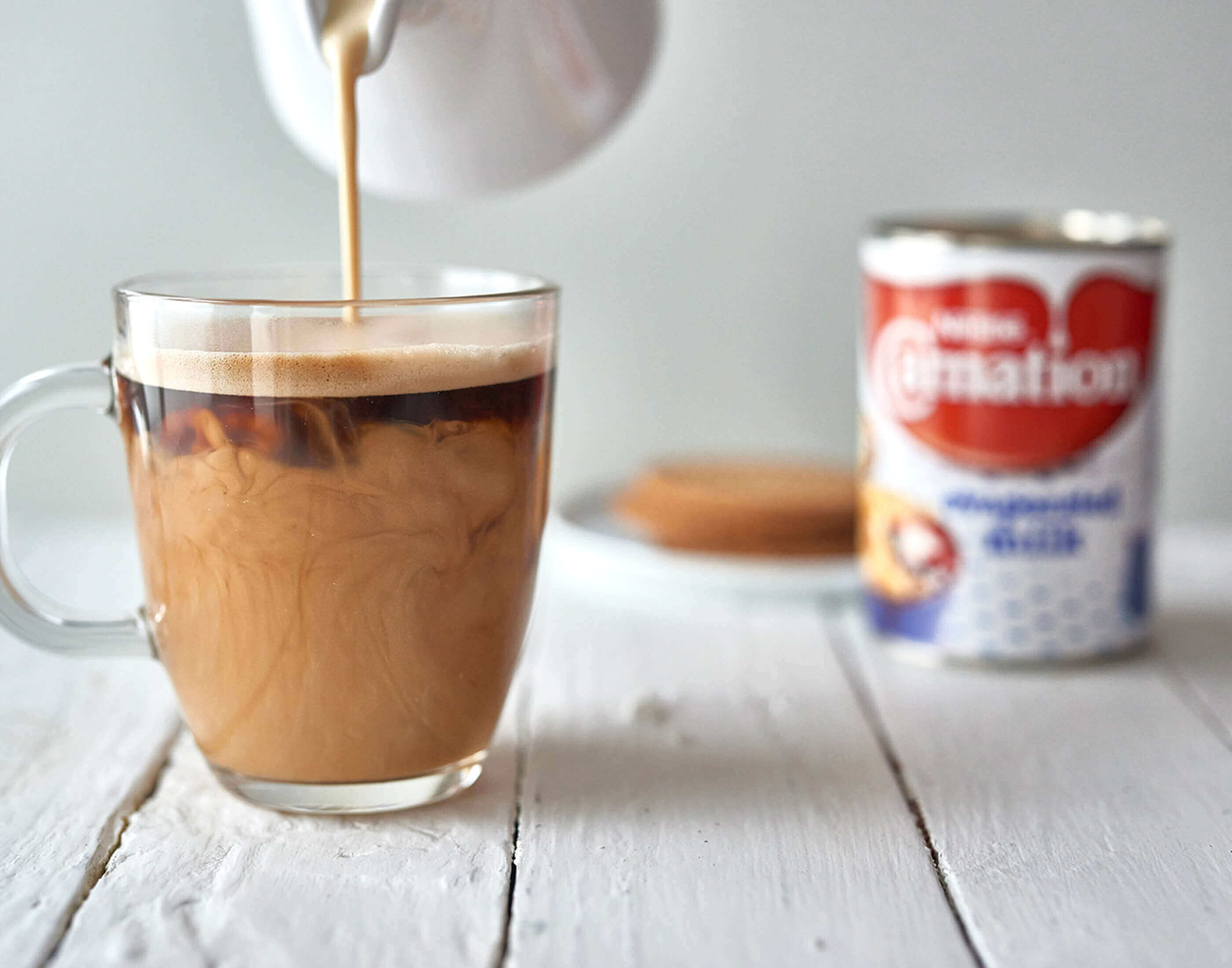 Evaporated milk poured in tea/coffee