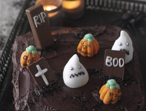 Graveyard Cake with pumpkins and ghosts made from icing
