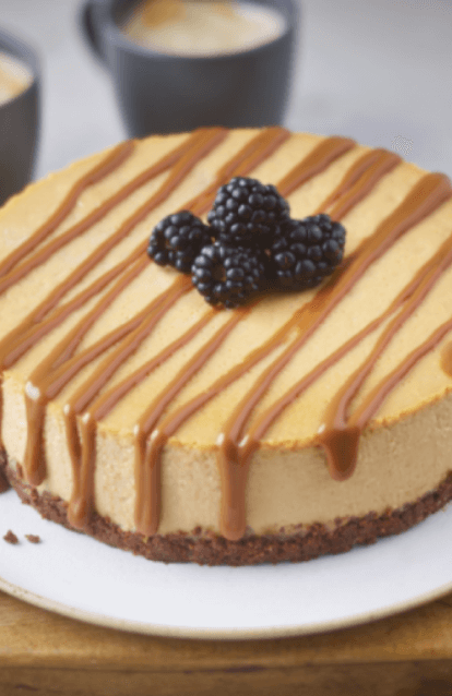salted caramel cheesecake with caramel drizzle and blackberries on top