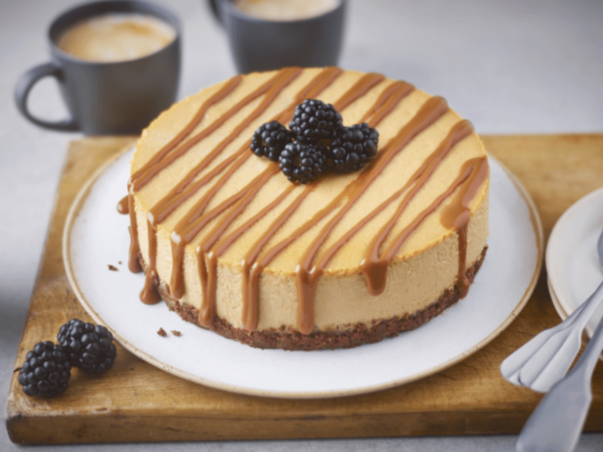 salted caramel cheesecake with caramel drizzle and blackberries on top sitting on a wooden board with coffee cups in the background